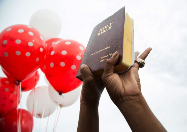 A community member holds up a bible during a vigil in memory of Alton Sterling.