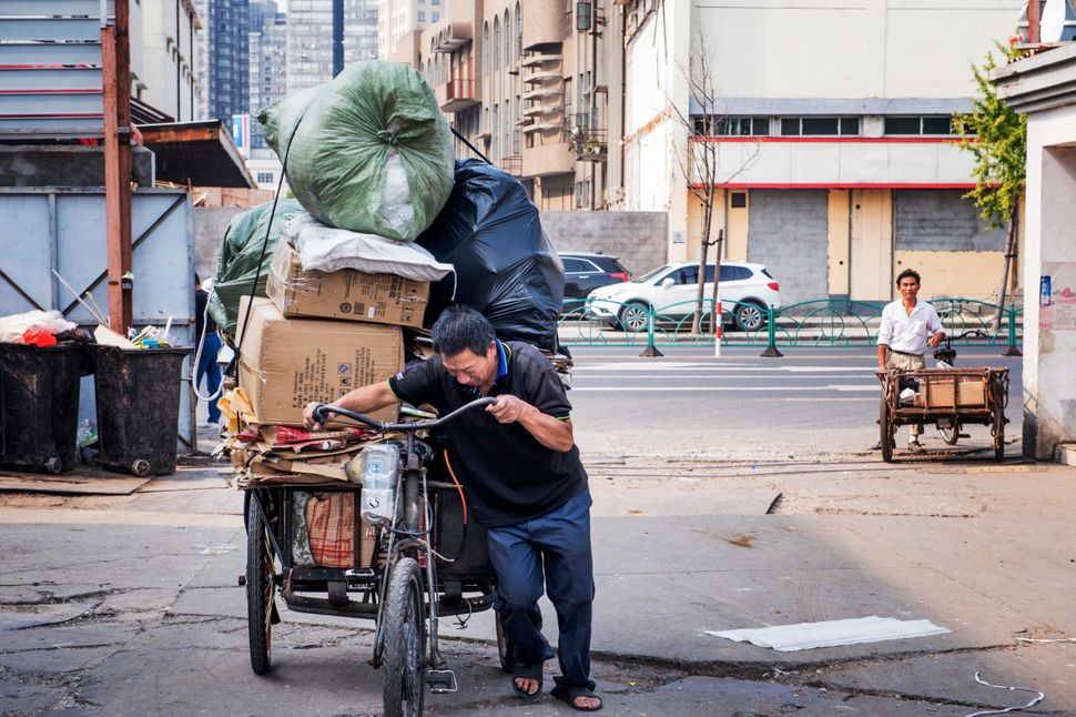 An informal recycler pushes his tricycle in Shanghai, China.