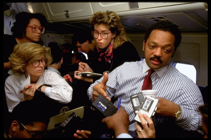 The Rev. Jesse Jackson speaks with reporters aboard a plane during a 1988 campaign stop in Ohio.