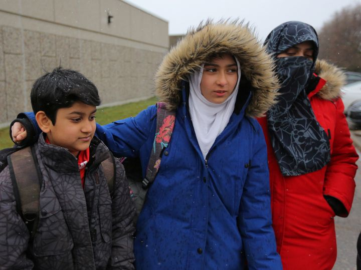 Khawlah Noman, 11, leaves Pauline Johnson Junior Public School with her mother Saima Samad (R) and brother Mohammed Zakariyya