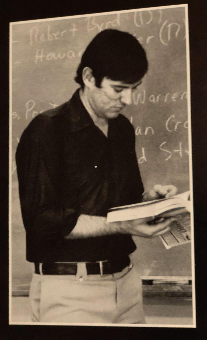 Myrrl Byler pausing in his teaching in front of the blackboard at Hartville Christian School.
