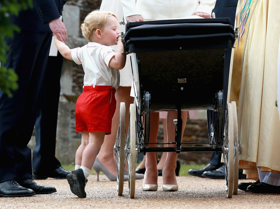 Prince George looks in Princess Charlotte's pram at her christening. Jackson: 'I just capture these sweet