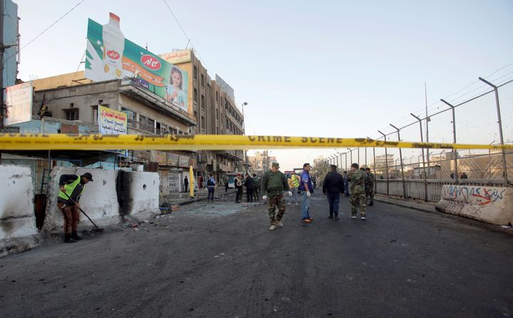 Iraqi security forces inspect the site of a bomb attack in Baghdad on Monday.