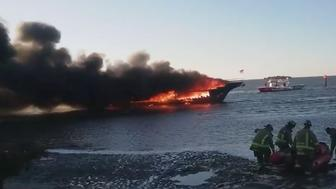 Firefighters are seen at the scene of a casino boat fire that left one person dead and more than a dozen other injured