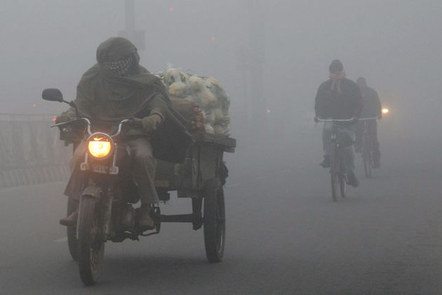 Indian commuters make their way through heavy air pollution and fog in