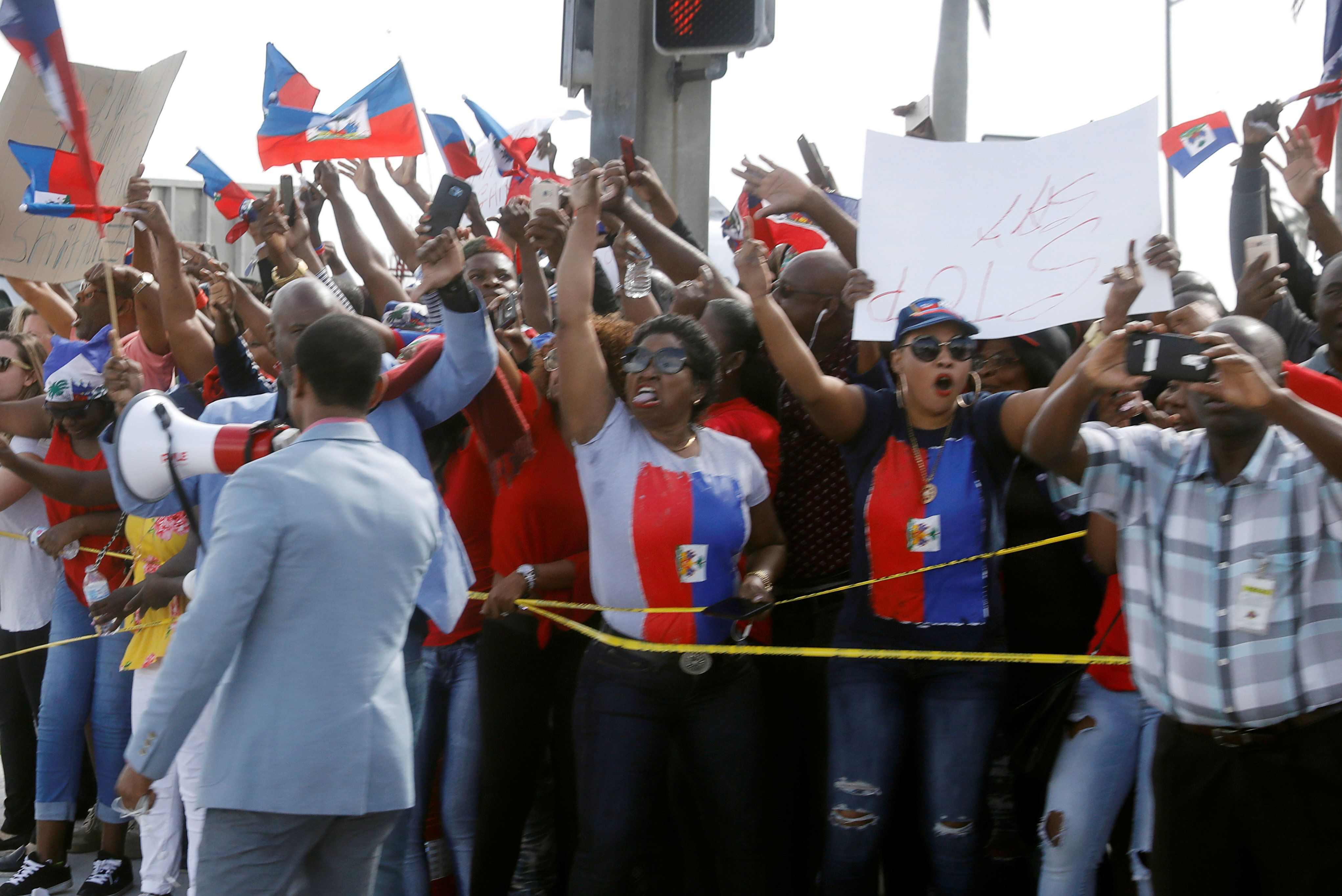 Demonstrators hold up Haitian flags and shout as President Donald Trump's motorcade passes in West Palm Beach, Florida,