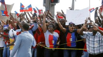Demonstrators hold up Haitian flags and shout as the motorcade of U.S. President Donald Trump passes in West Palm Beach, Florida, U.S., January 15, 2018.  REUTERS/Kevin Lamarque