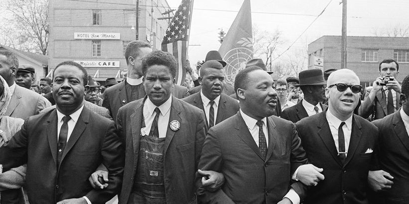 Dr. Martin Luther King, Jr. locks arms with his aides as he leads a march of several thousands on March 17, 1965 in Montgomer