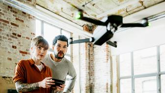Two young entrepreneurs testing a drone and flying it indoors