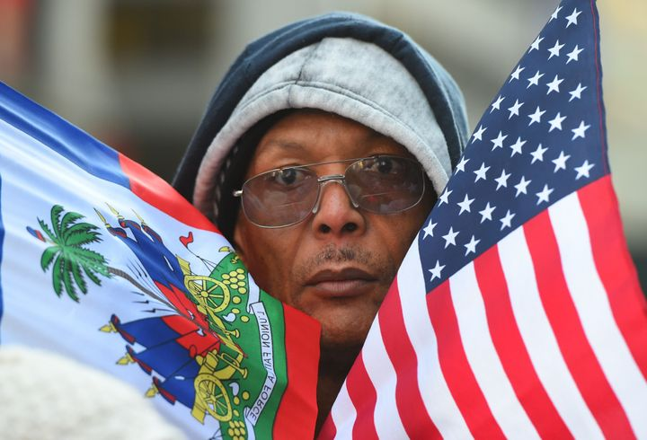 Protestor Pierre Gabriel from Haiti carries flags during a march on Martin Luther King, Jr. Day in Times Square.