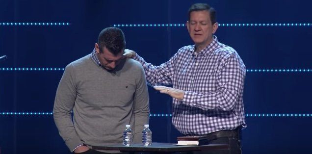 Highpoint's lead pastor Chris Conlee prays for Savage.