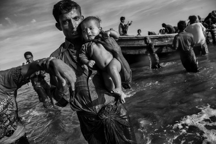 COX'S BAZAR, BANGLADESH - OCTOBER 01: A Rohingya refugee man carries a baby after arriving by boat to Bangladesh side of the