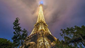 Landmark of Paris, France. Eiffel tower in one day with mist in the sky and lighting from the tower.