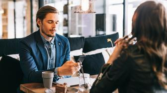 Man using his smartphone on a date, ignoring the person he's with.