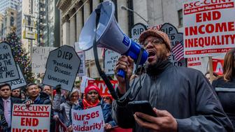 NEW YORK STOCK EXCHANGE - WALL STREET, NEW YORK, UNITED STATES - 2017/12/19: Reverend Brian Gibbs of the New York Council of Churches - About 500 protesters chanting Kill the Bill, Dont Kill Us! filled the street outside the New York Stock Exchange on December 19, 2017; where the resources siphoned from the poor and middleclass by the Republican tax bill will be concentrated. More than 60 people lay down in the street for a die-in and 15 protesters were arrested blocking access to the Stock Exchange. (Photo by Erik McGregor/Pacific Press/LightRocket via Getty Images)
