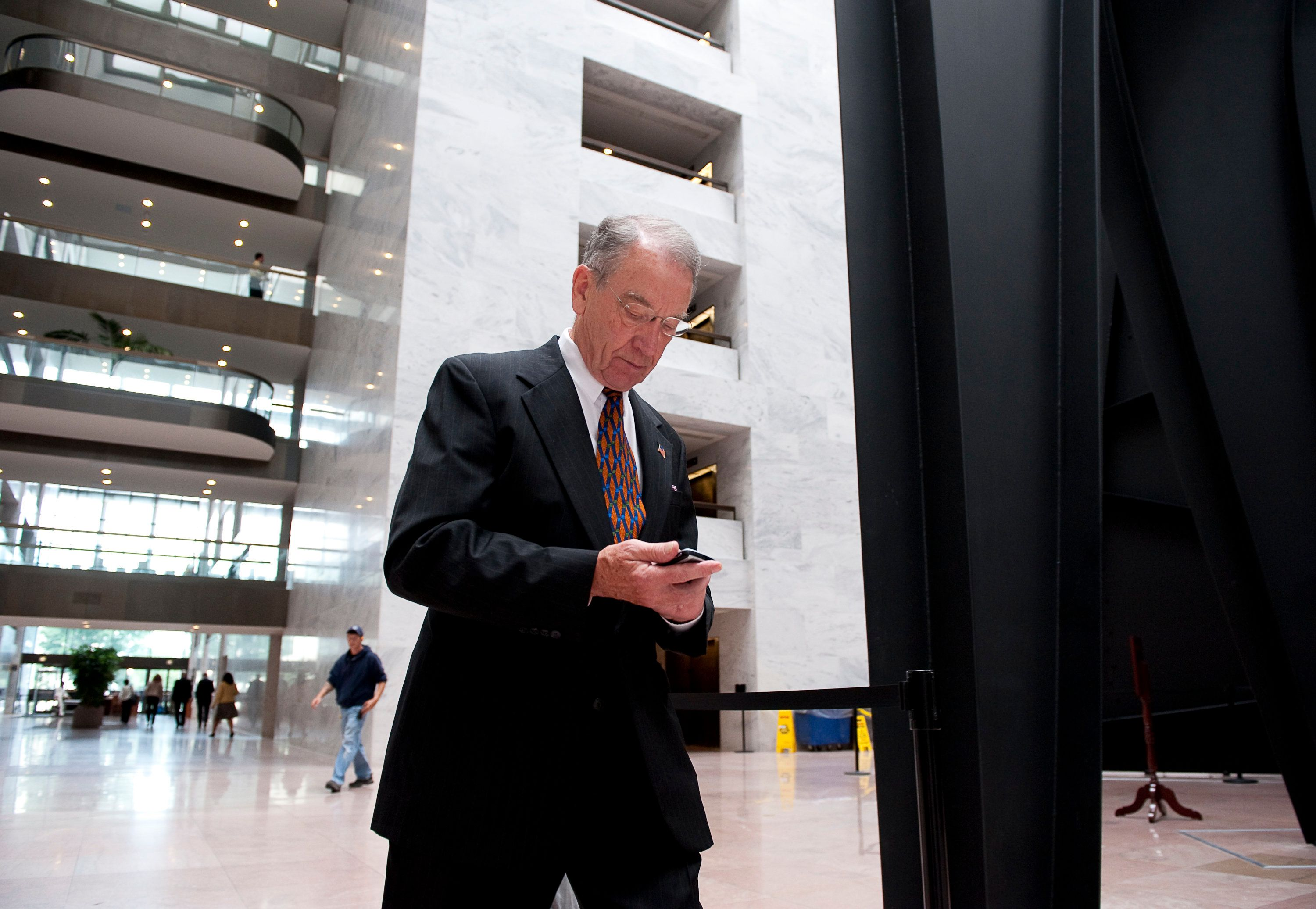 Sen. Charles Grassely, R-Iowa, sends out a tweet while he walks from his office to a press interview, June 16, 2009. Grassley is one of an estimated 30 senators and more than 100 House members who use Twitter, quite a development in an institution where messengers still bow when they enter the Senate chamber.  (Photo by Cliff Owen/MCT/MCT via Getty Images)
