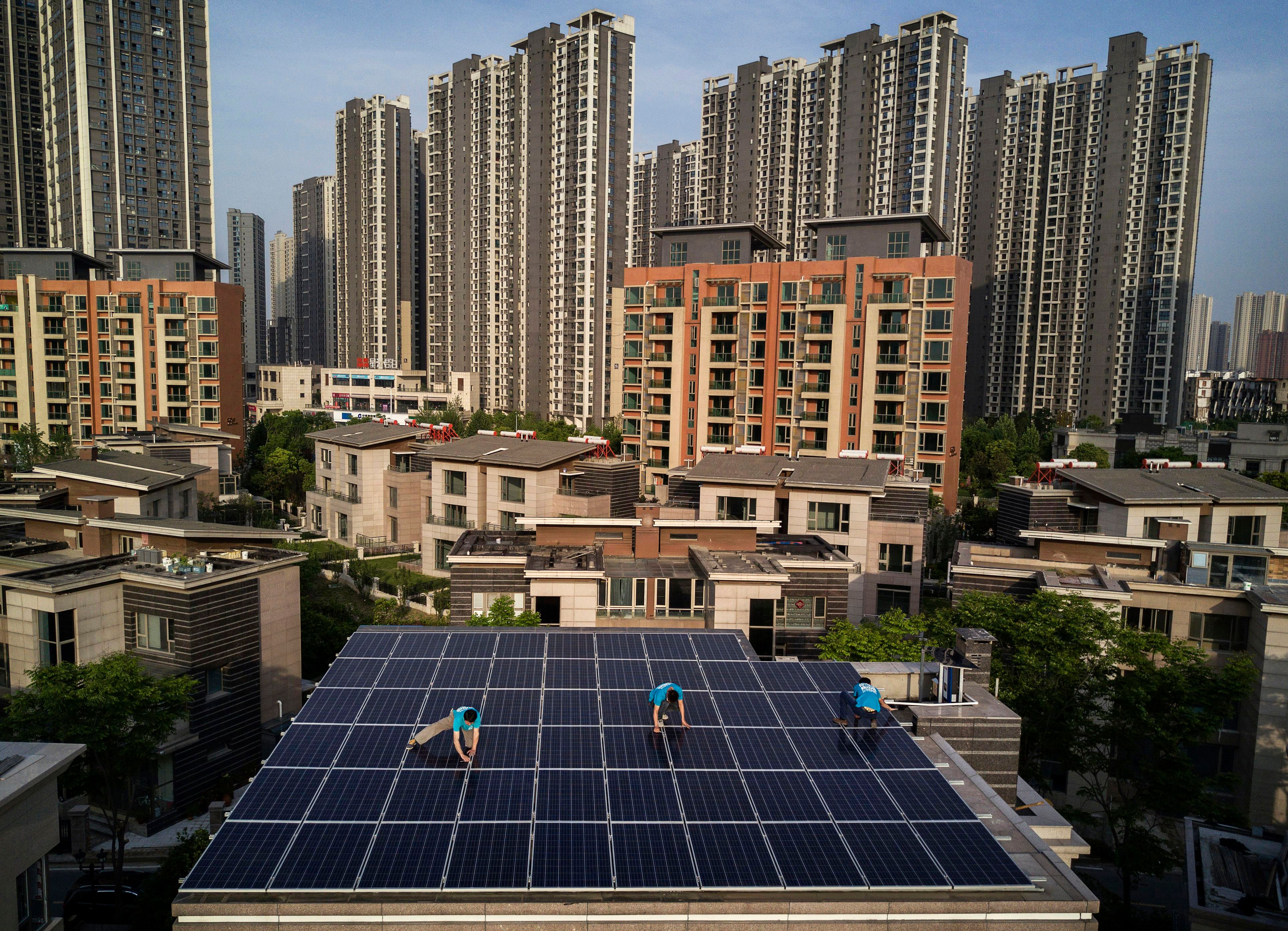 Workers from Wuhan Guangsheng Photovoltaic Company install solar panels on the roof of a building in Wuhan, China. In Au