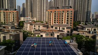 WUHAN, CHINA - APRIL 27: Chinese workers from Wuhan Guangsheng Photovoltaic Company install solar panels on the roof of a building  on April 27, 2017 in Wuhan, China. As the world's most populated nation, China consumes more electricity and creates more carbon emissions than any other country.  Yet it is also the world's leader in renewable energy, known for its sprawling solar fields and large-scale wind turbine projects in western rural areas.  Greenpeace estimates that by 2030 renewable energy could replace fossil fuels as China's primary source of power. However, much of the energy being produced by rural projects is wasted during transmission to urban areas or by rising curtailment rates (a measure of potential supply lost to low consumption).  To harness the potential for renewable energy to power China's expanding cities, solar and wind projects are increasingly being brought into urban areas where supplies can be generated and consumed locally. In Wuhan, a relatively small Chinese city with a population of 10.6 million, rooftop solar panel systems being installed on houses and buildings to provide energy and subsidies to owners.  Any surplus energy is sold to the state power grid, though there are often delays in bringing new renewable projects into the grid system. Still, the concept is slowly gaining acceptance among urban consumers who find it increasingly accessible, according to Wuhan Guangsheng Photovoltaic Company, which is responsible for more than 80 percent of the city's installations.  To ease the country's longtime dependence on coal and other fossil fuels, China's government has made strategic investments in the solar panel industry which has created intense global competition in the estimated $100 billion global solar energy market.(Photo by Kevin Frayer/Getty Images)