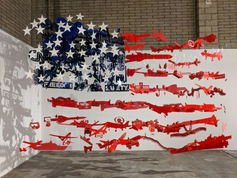 This powerful piece of artwork on display at the INTO ACTION! exhibit looks like the American flag from one angle and looks l