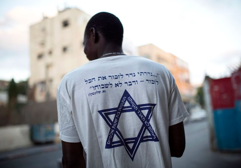 "<em>An African migrant wears a T-shirt with a Hebrew phrase referring to the Holocaust,"" I promise to remember... and ne"