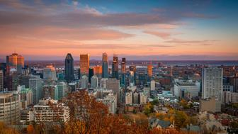 View of the skyline of downtown Montreal at sunset with orange and pink hues in the clouds, viewed from the Mont-Royal overlook.