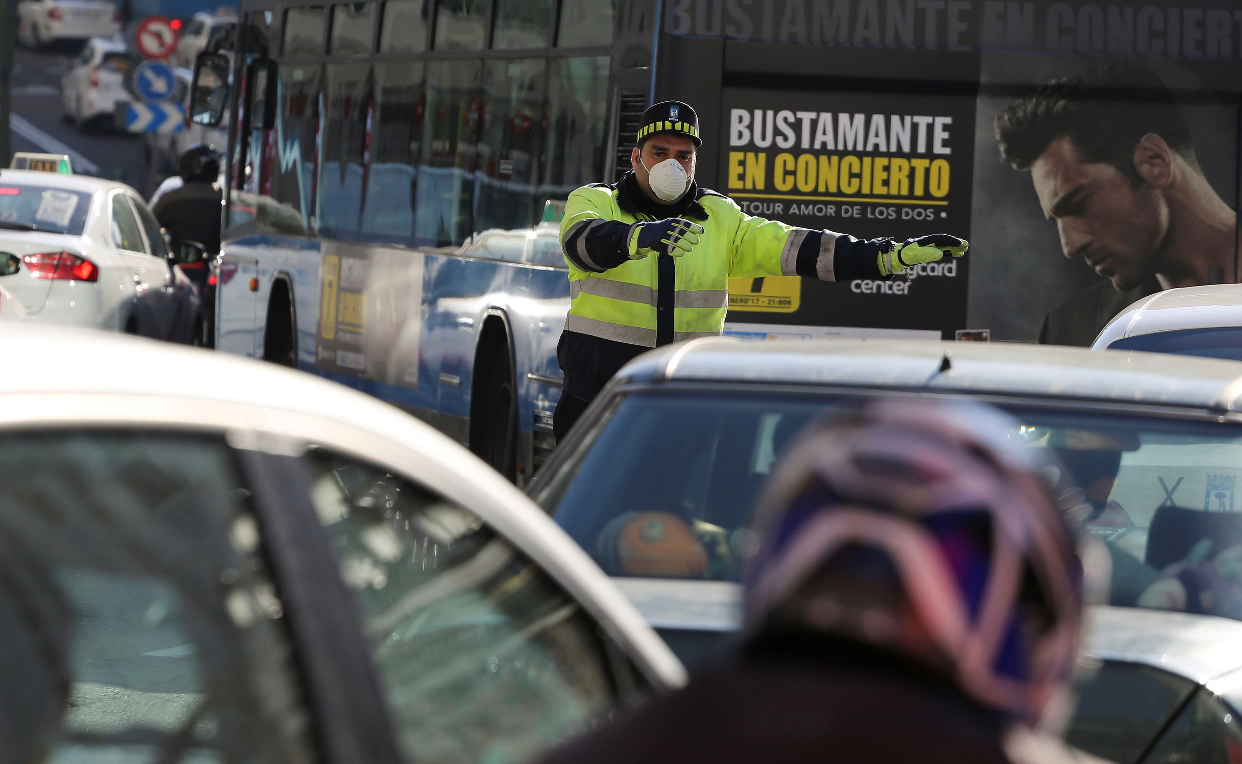 A traffic policeman wears a mask while directing traffic in Madrid on Dec. 29, 2016.