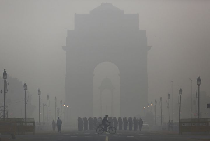 A man rides his bicycle in front of India gate in New Delhi.