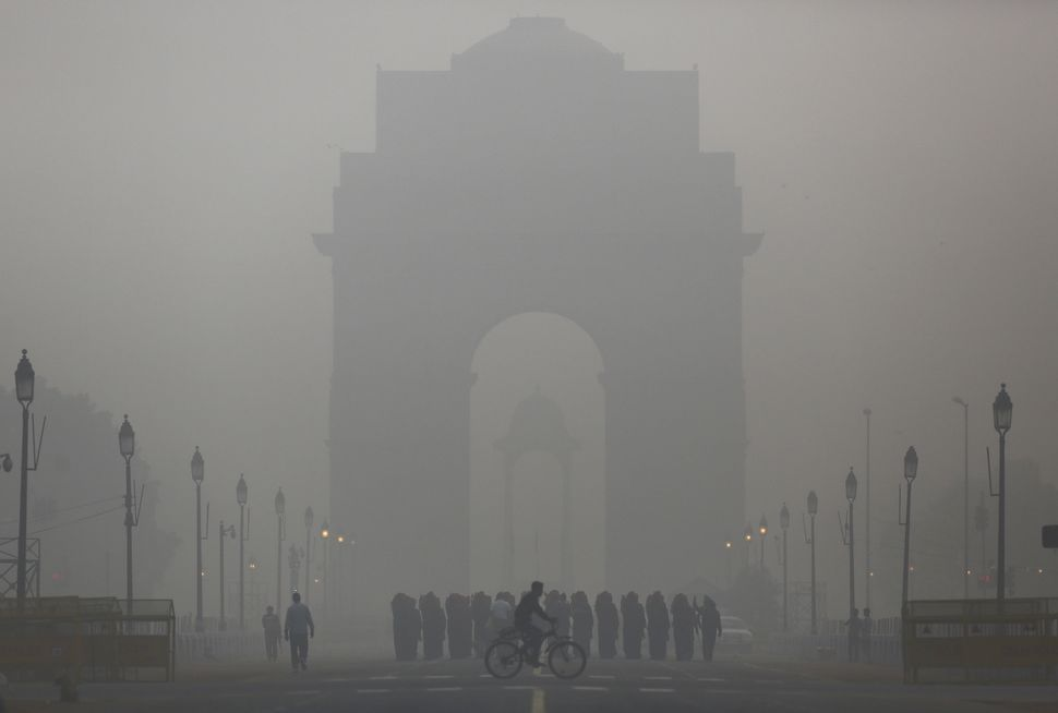 A man rides his bicycle in front of India gate in New