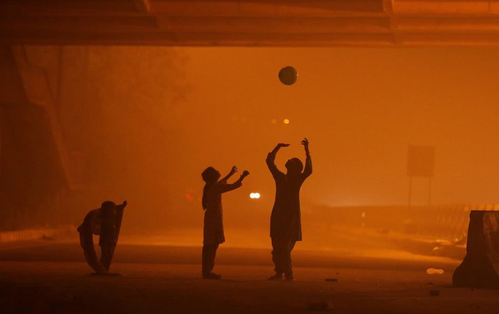 Girls play with a balloon amid heavy smog in New