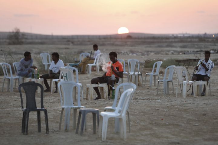 Detained African immigrants spend their free time outdoors in a makeshift cafe outside the Holot detention center, located in
