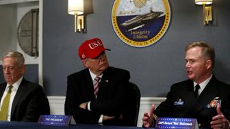 U.S. President Donald Trump (C, in red hat) and Defense Secretary James Mattis (L) receive a briefing with Commanding Officer U.S. Navy Captain Rick McCormack (R) aboard the pre-commissioned U.S. Navy aircraft carrier Gerald R. Ford at Huntington Ingalls Newport News Shipbuilding facilities in Newport News, Virginia, U.S. March 2, 2017. REUTERS/Jonathan Ernst