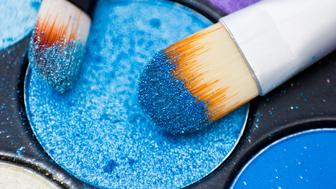 Brushes for make-up on the eye shadow palettes. Texture of crumbly  blue sparkling shadows.
