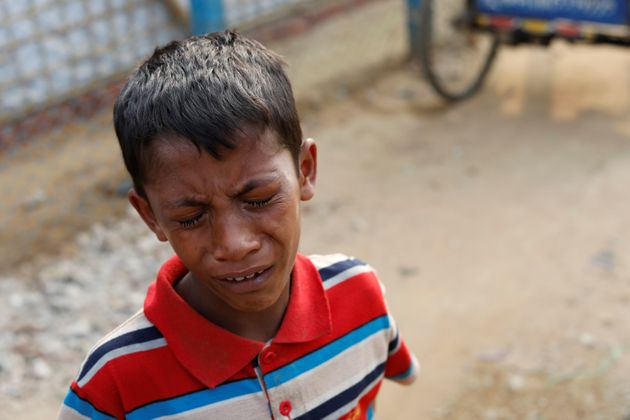 A young Rohingya boys cries outside a hospital in the Kutupalong refugee camp after learning his...