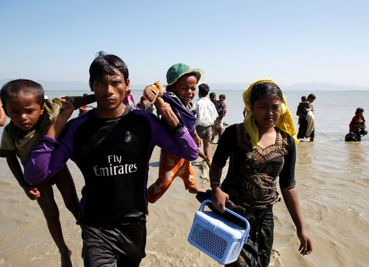 A Rohingya refugee man holding children walks towards the shore as they arrive on a makeshift boat after crossing the Banglad