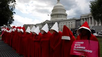 "REFILE - ADDITIONAL CAPTION INFORMATION  Women dressed as handmaids from the novel, film and television series ""The Handmaid's Tale"" demonstrate against cuts for Planned Parenthood in the Republican Senate healthcare bill at the U.S. Capitol in Washington, U.S., June 27, 2017.  REUTERS/Aaron P. Bernstein"