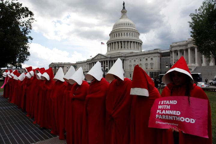 "Women dressed as handmaids from ""The Handmaid's Tale"" demonstrate against cuts for Planned Parenthood in the Republican Senat"