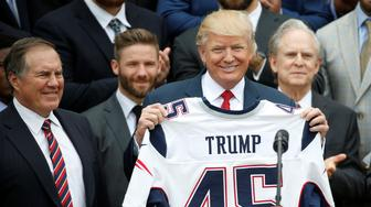 U.S. President Donald Trump holds up a New England Patriots jersey as Head Coach Bill Belichick (L) watches during an event honoring the Super Bowl champion New England Patriots at the White House in Washington, U.S., April 19, 2017. REUTERS/Joshua Roberts     TPX IMAGES OF THE DAY