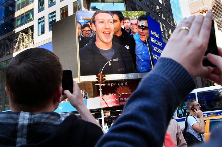 Facebook CEO Mark Zuckerberg's celebration after the company's IPO launch is seen on a screen in New York City.