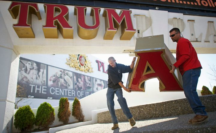 Workers remove the sign from Trump Plaza Casino in Atlantic City, New Jersey, Oct. 6, 2014, after Trump sued to end a licensi
