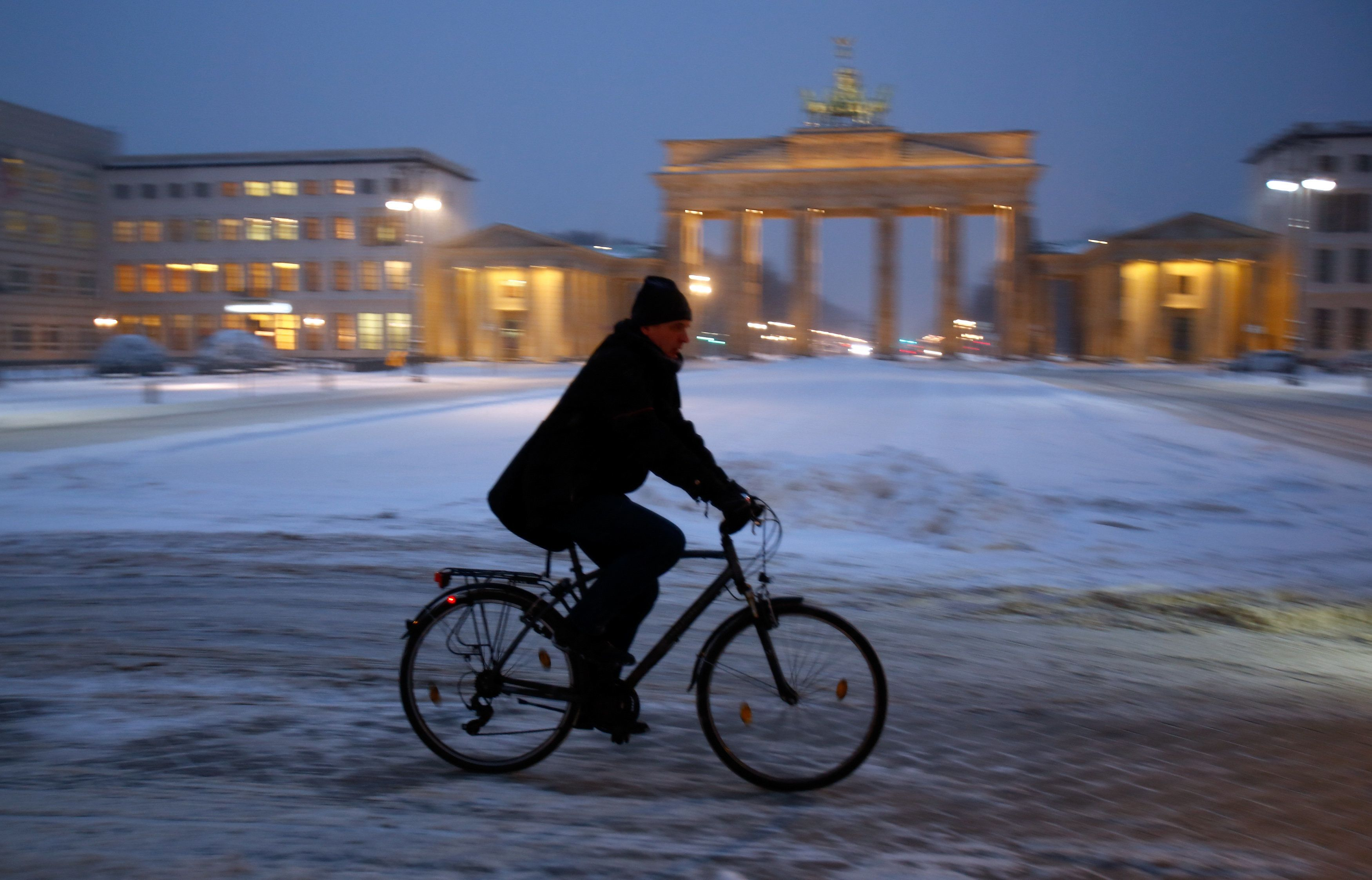 A cyclist rides his bicycle during heavy snowfall near Berlin's landmark Brandenburg Gate, Germany, January 6, 2016.    REUTERS/Hannibal Hanschke