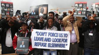 African asylum seekers, mostly from Eritrea, who entered Israel illegally during the past years, hold placards showing migrants who they say were killed after being deported to their country, during a protest against Israel's deportation policy in front of the Supreme Court in Jerusalem on January 26, 2017. / AFP / MENAHEM KAHANA        (Photo credit should read MENAHEM KAHANA/AFP/Getty Images)