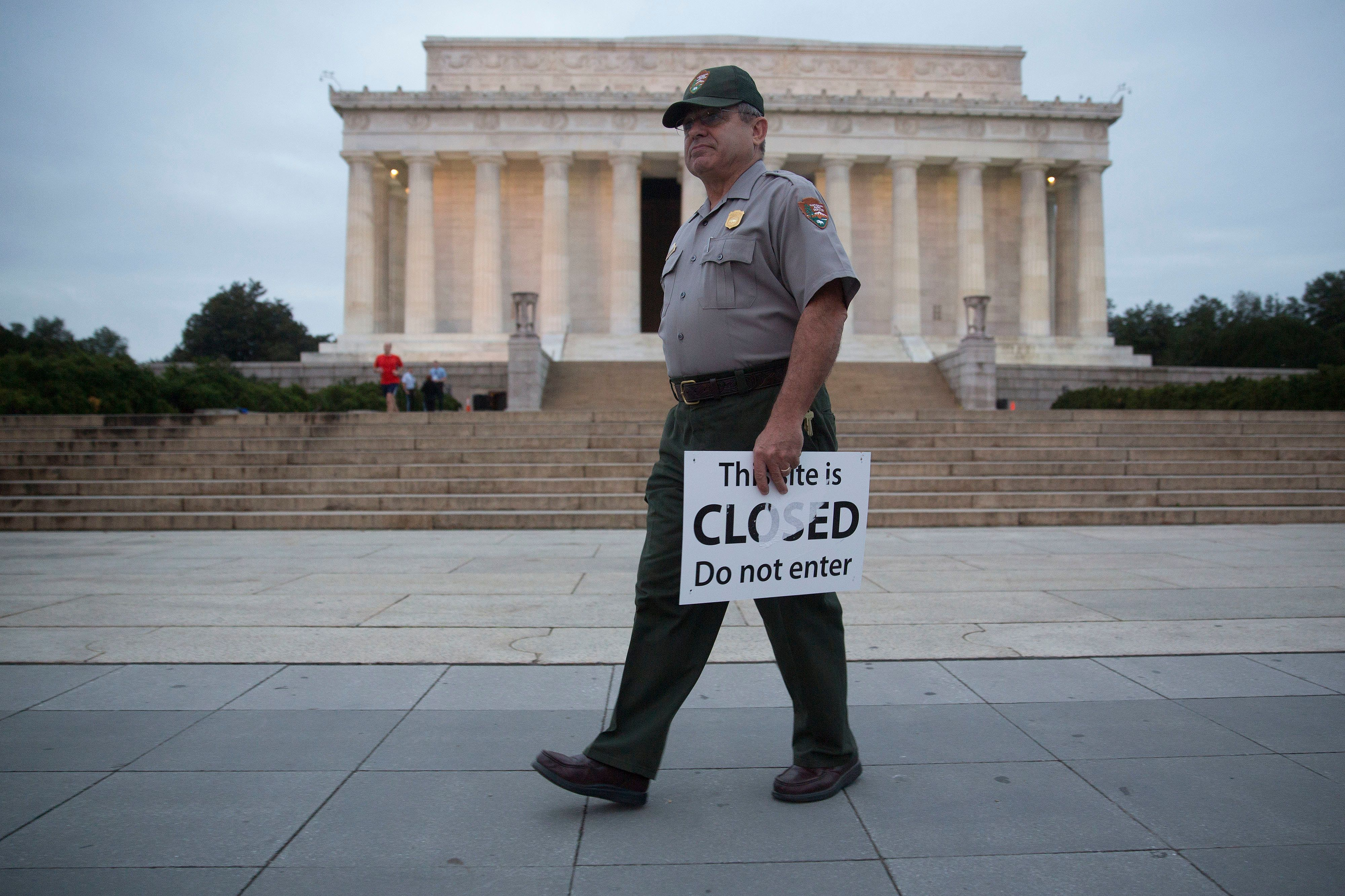 A National Park Service rangerremoves a closed sign from the Lincoln Memorial after the 2013 shutdown.