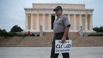 National Park Service park ranger Richard Trott holds a closed sign he removed at the Lincoln Memorial in Washington, D.C., U.S., on Thursday, Oct. 17, 2013. After the partisan passions and heated rhetoric, the disruptions of a government shutdown and displays of dysfunction, Congress did what it could have done weeks ago: voted to fund the government and lift the debt limit. Photographer: Andrew Harrer/Bloomberg via Getty Images