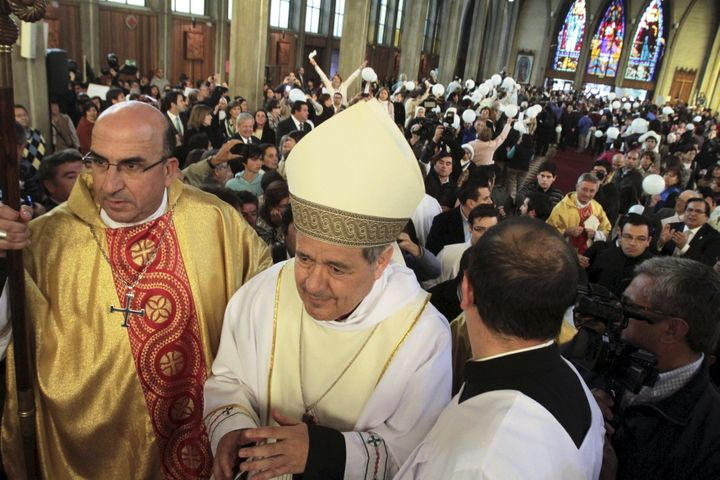 Bishop Juan Barros, center, attends his first religious service as citizens protest at the Osorno cathedral south of Santiago
