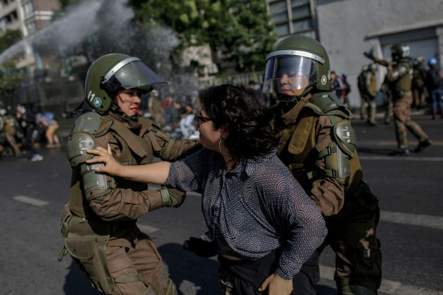 Police officers confront a demonstrator during a protest against Pope Francis in Santiago...