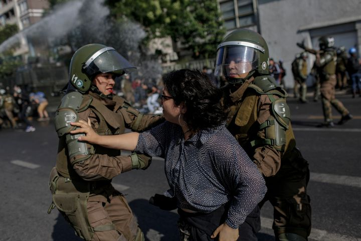 Police officers confront a demonstrator during a protest against Pope Francis in Santiago on Tuesday.
