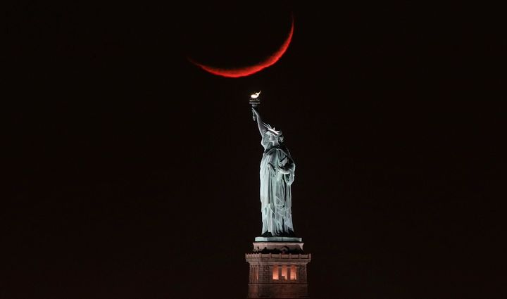 A crescent moon sets behind the Statue of Liberty on Jan. 19, 2018 in New York City.