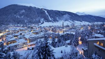 FILE: St. John's church, centre right, sits surrounded by snow-covered residential buildings as night falls in Davos, Switzerland, on Monday, Jan. 18, 2015. President Donald Trump will dominate the Davos forum as no U.S. leader has before: a provocateur-in-chief practiced at tweaking the elites wholl gather later this month to celebrate the global order he seems eager to tear down. Trump would be the first sitting American president to attend the meeting of bankers, corporate chiefs, academics and investors since Bill Clinton in January 2000. Our editors select the best archive images from Davos and the Trump Presidency. Photographer: Matthew Lloyd/Bloomberg via Getty Images
