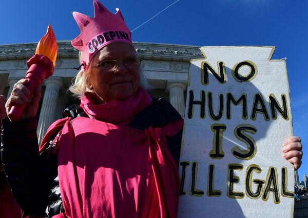 A woman dressed as Lady Liberty displays a sign on the steps of the Lincoln Memorial.