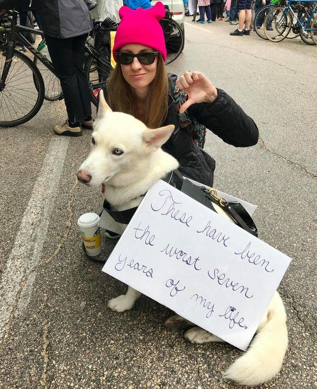 Stephanie Rzepka and her dog Hattie, wearing a sign reading